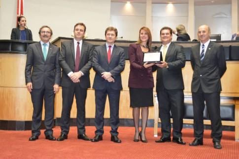 Deputada Renata Bueno recebe a homenagem das mãos do propositor da Sessão Solene, Cleiton Salvaro. Foto: Eliana Maccari – Jornal Vanguarda
